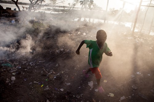 A boy runs through the smoke of burning garbage near the Niger River in Bamako, Mali on December 9th, 2012.